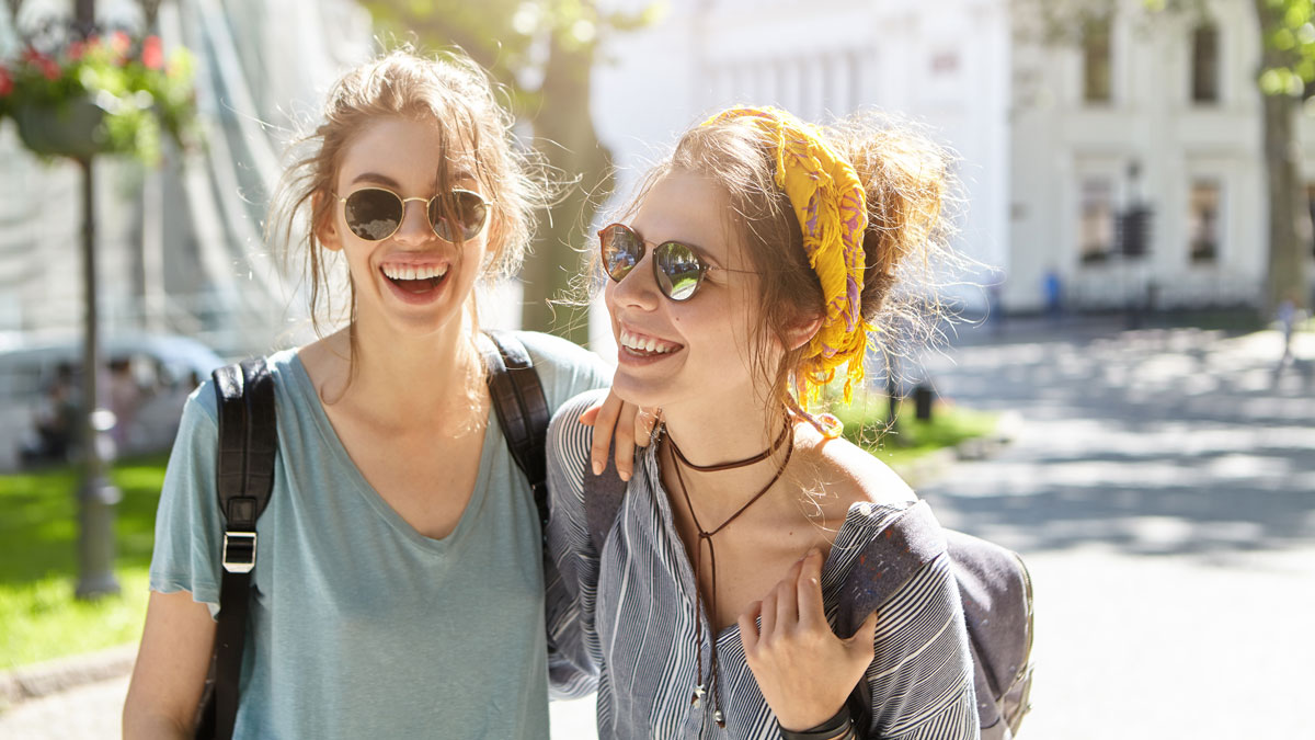 Outdoor portrait of two female comrades walking on street laughing while talking with each other enjoying summer vacations. Two teenagers in sunglasses holding rusksacks on backs going on picnic